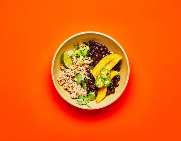 A Cuban Black Bean bowl on an orange table