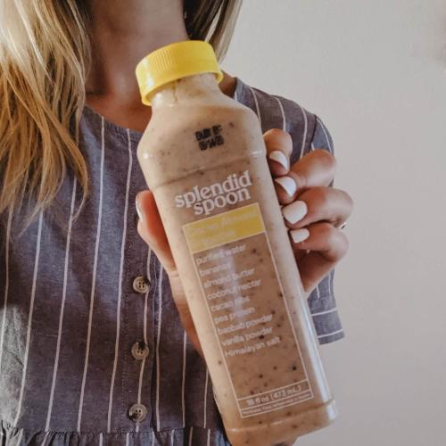 Woman in striped dress holding cacao almond smoothie.