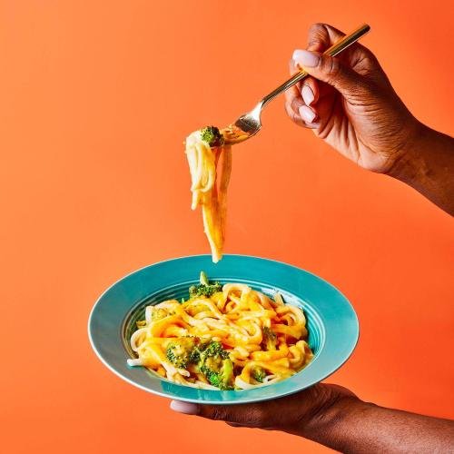 Creamy Butternut Squash Noodles in a dish being held by a woman on an orange background.