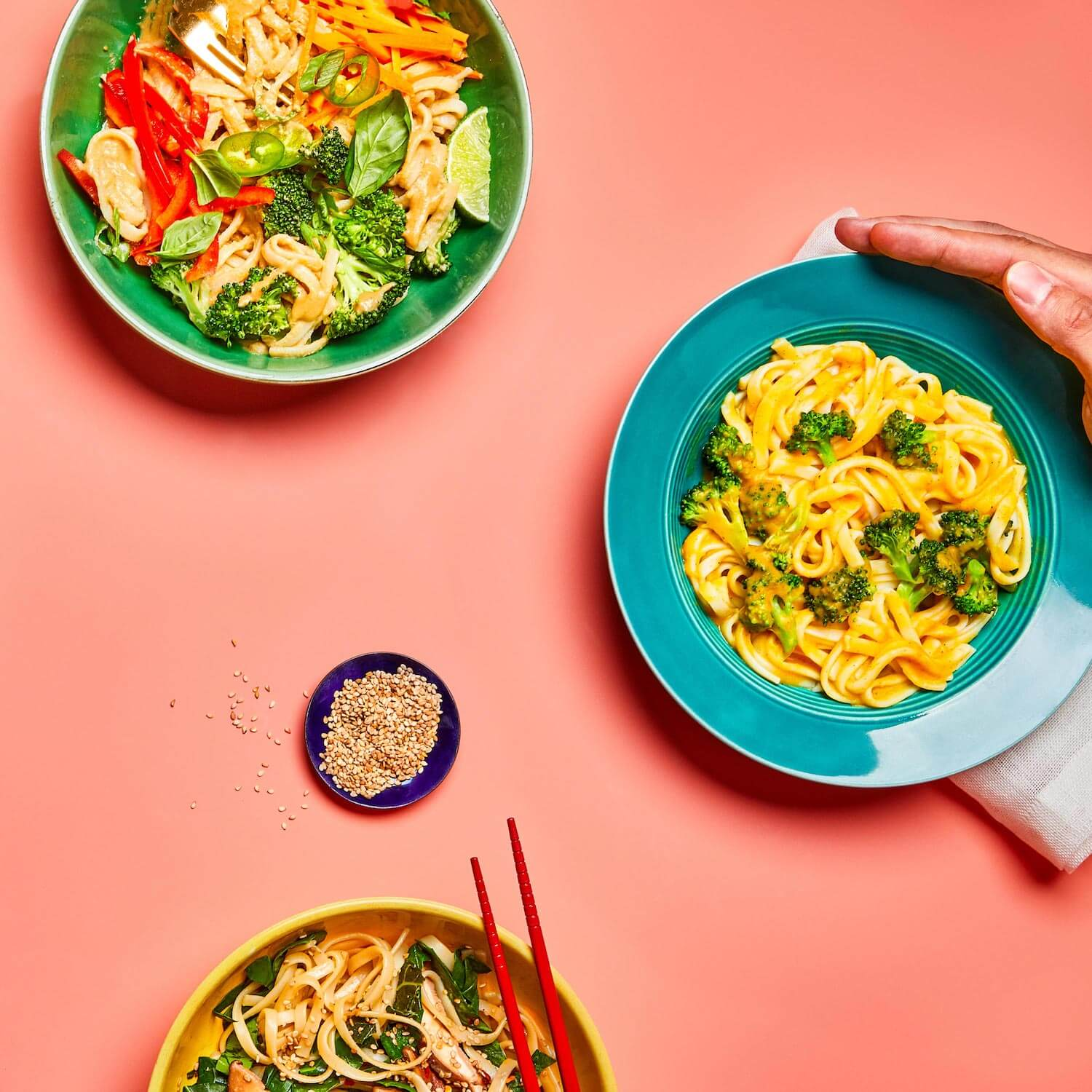 Creamy Butternut Squash Noodles in a dish with 2 other noodle dishes on a peach background.