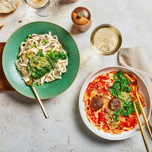 Creamy Spinach & Mushroom Noodles and Vegan Meatballs & Marinara Noodles on a table with utensils.