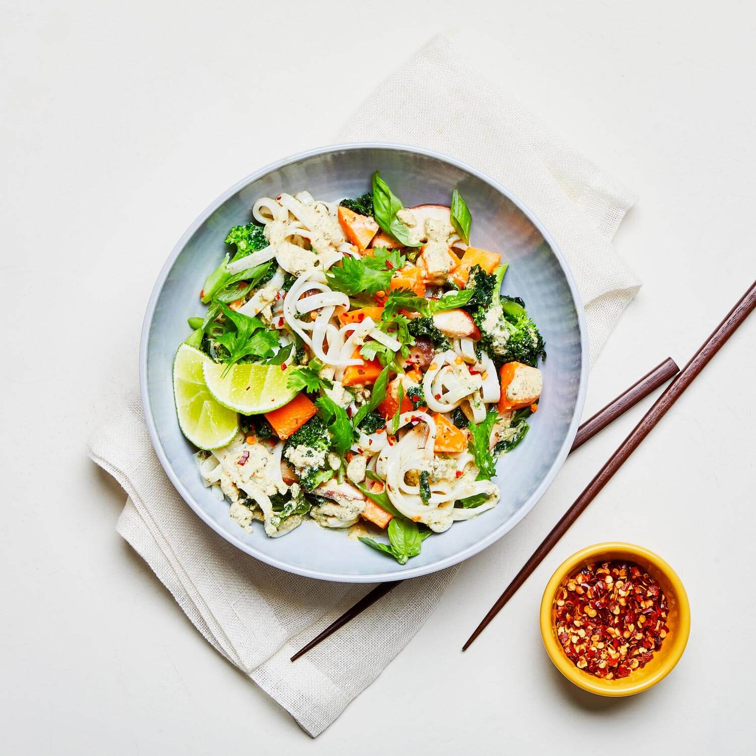 Green Curry in a dish with a napkin, chopsticks, and a dish of red pepper flakes on the table.