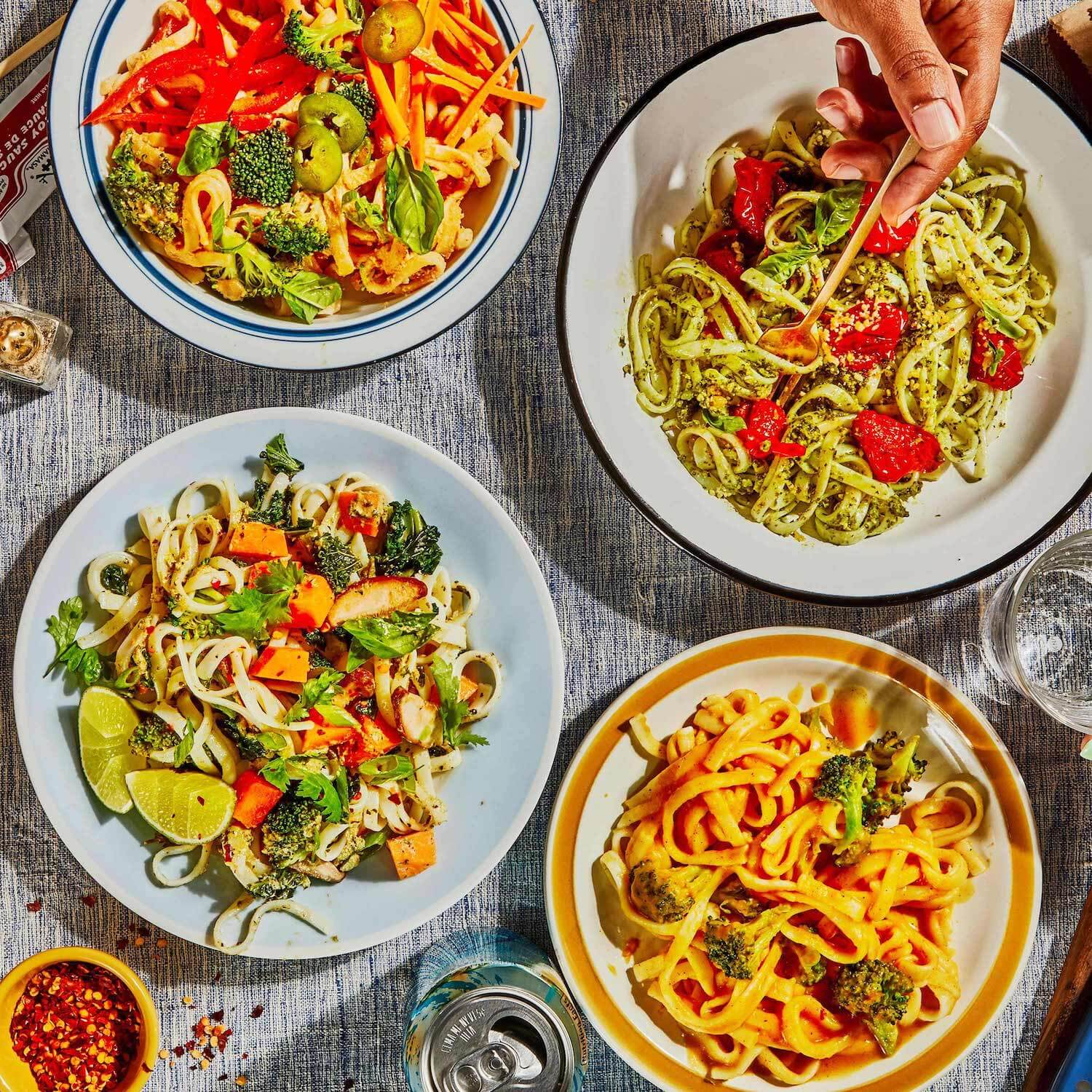 A table-setting of 4 different noodle dishes with someone twisting one of the noodles onto a fork.