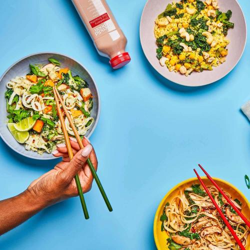 Green Curry Noodles being picked up by a woman with chopsticks, on a table with 2 other dishes and a smoothie.