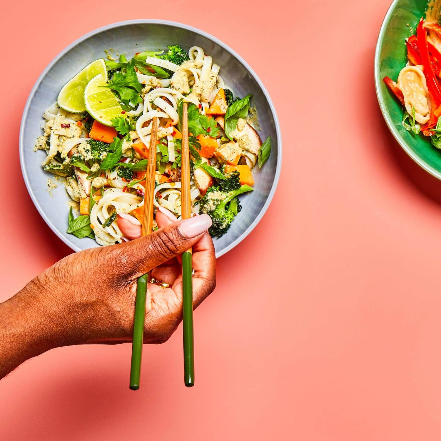 Green Curry Noodles in a dish being picked up by a woman holding chopsticks.