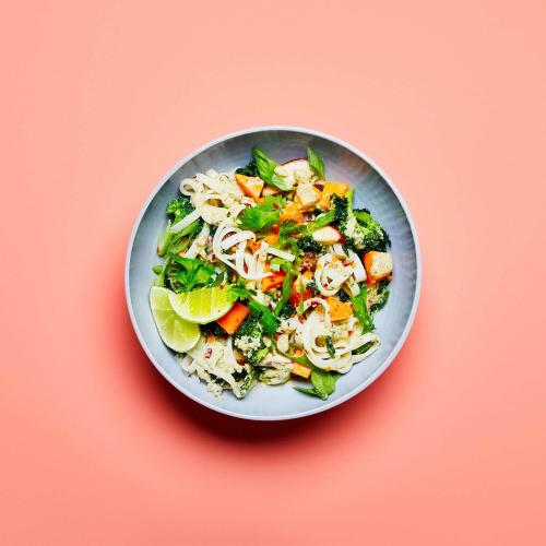 Green Curry Noodles in a dish on a peach background.