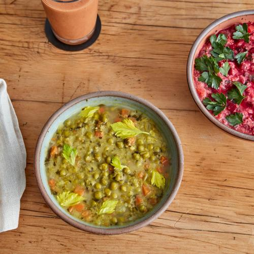 Blue bowl of Green Split Pea, Clay bowl of Red Beet Buddha Bowl on wooden background.