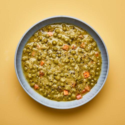 Gray bowl of Green Split Pea on yellow background.