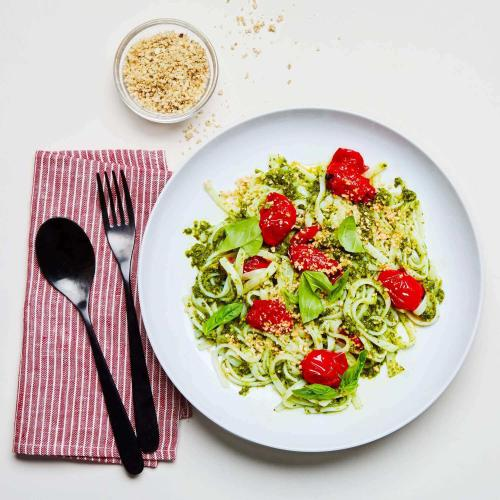 Kale Pesto Noodles on a plate with a napkin, utensils, and small dish of plant-based parmesan.