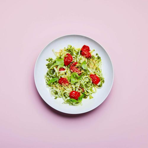 Kale Pesto Noodles in a dish on a pink background.