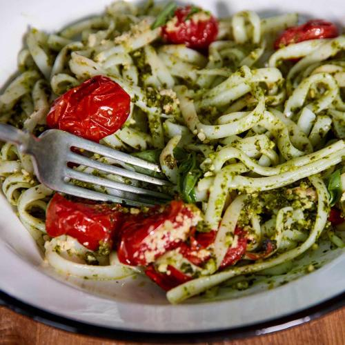 A close-up photo of Kale Pesto Noodles with a fork in the dish.