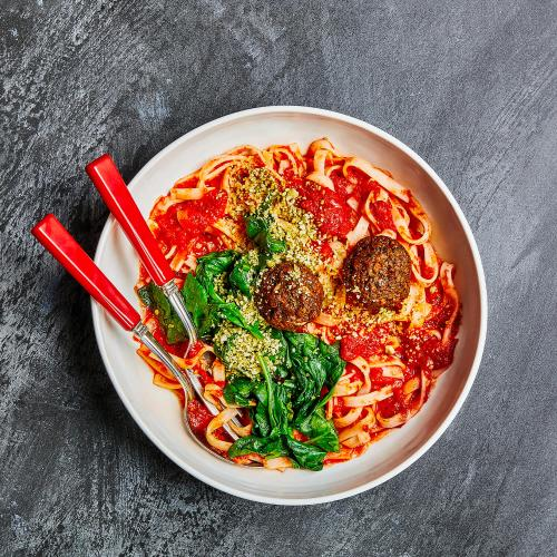 Vegan Meatballs & Marinara Noodles on a black table