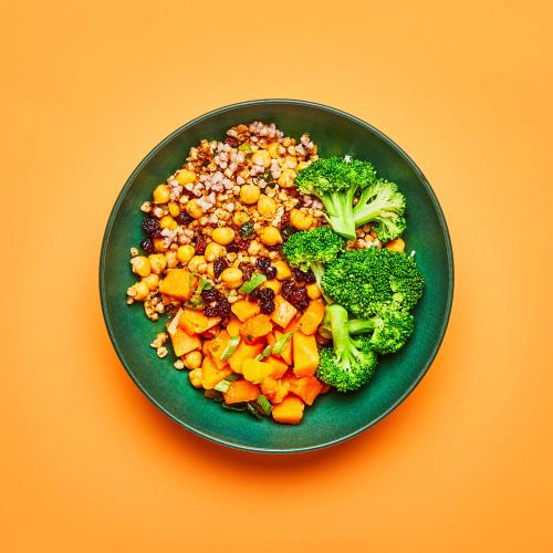 Moroccan Spiced Buckwheat Bowl in green bowl on orange background.