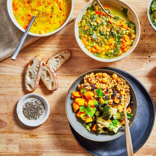 White bowl of Red Lentil Dal with spoon, white bowl of lentil kale with gold spoon, gray bowl of moroccan spiced buckwheat bowl on darker gray plate with gold spoon, small dish of pepper and salt with sliced bread all on a wooden background.