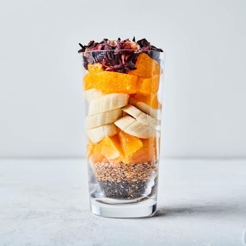 Clear glass with chia seeds, flax seeds, oranges, bananas and hibiscus with a white background.