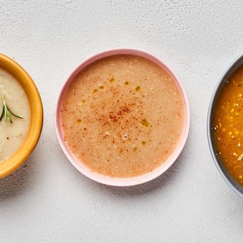 Cauliflower Potato Chowder in yellow bowl, parsnip apple puree in pink bowl, pumpkin pear bisque in blue bowl on white background.