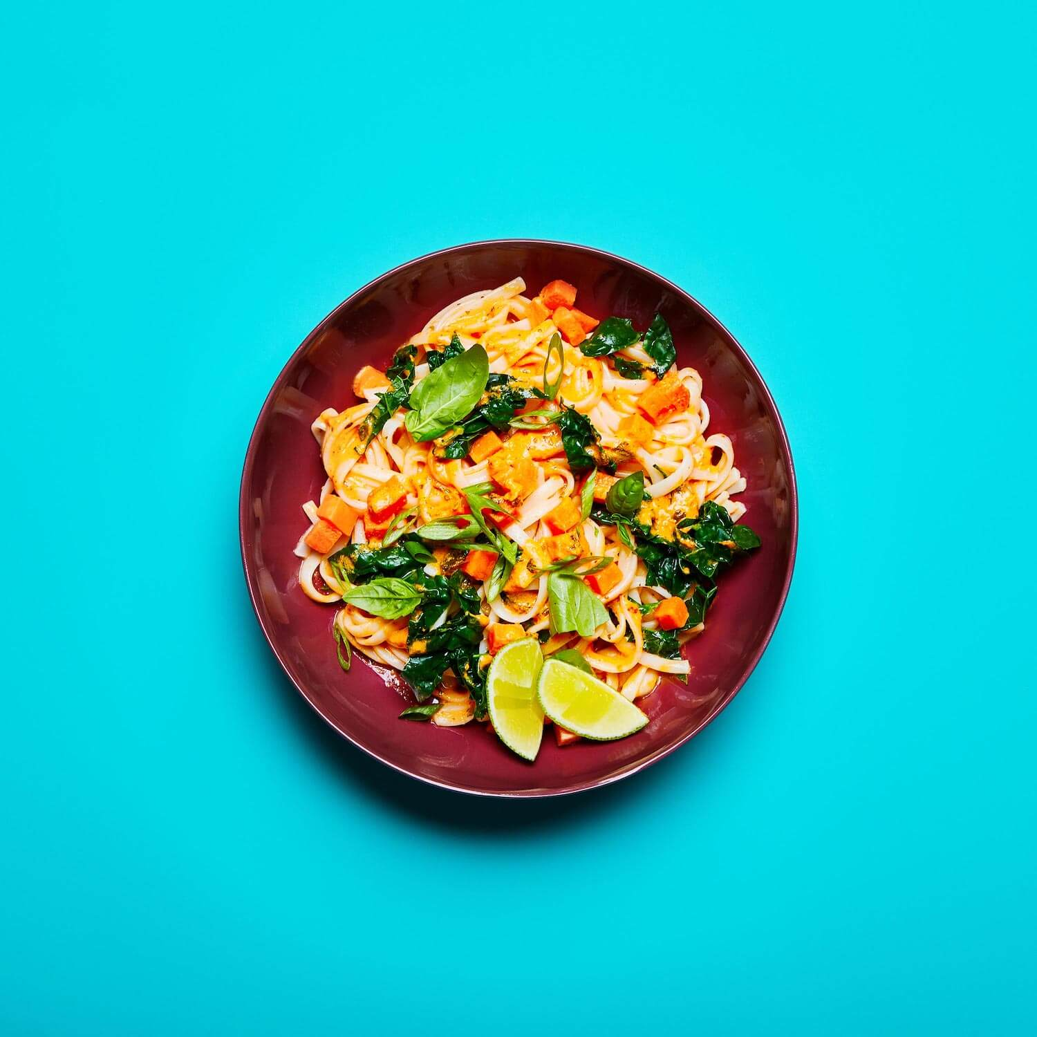 Red Curry Noodles in a dish on a blue background.