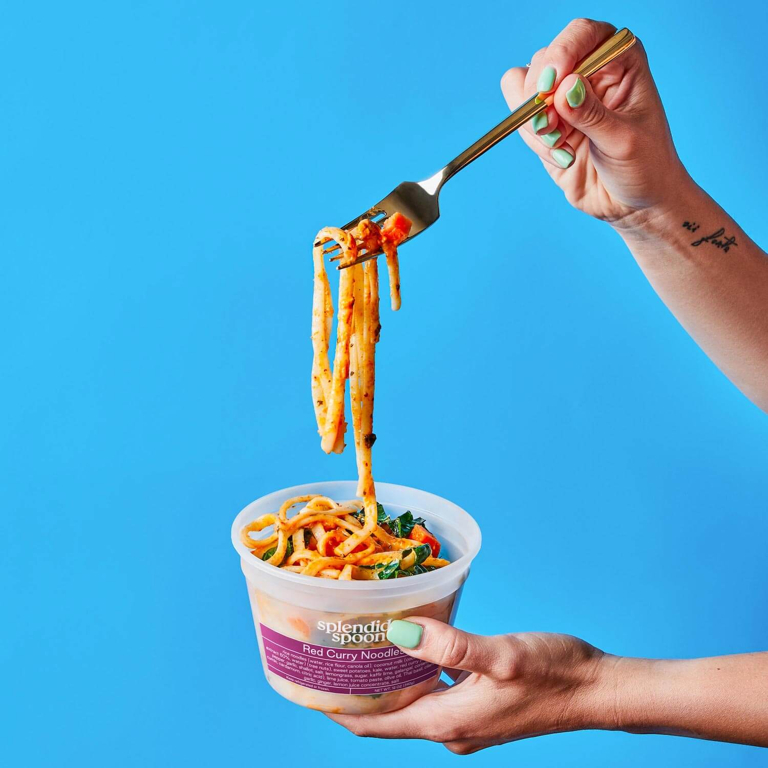 Red Curry Noodles in a Splendid Spoon container, being held by a woman in front of a blue background.