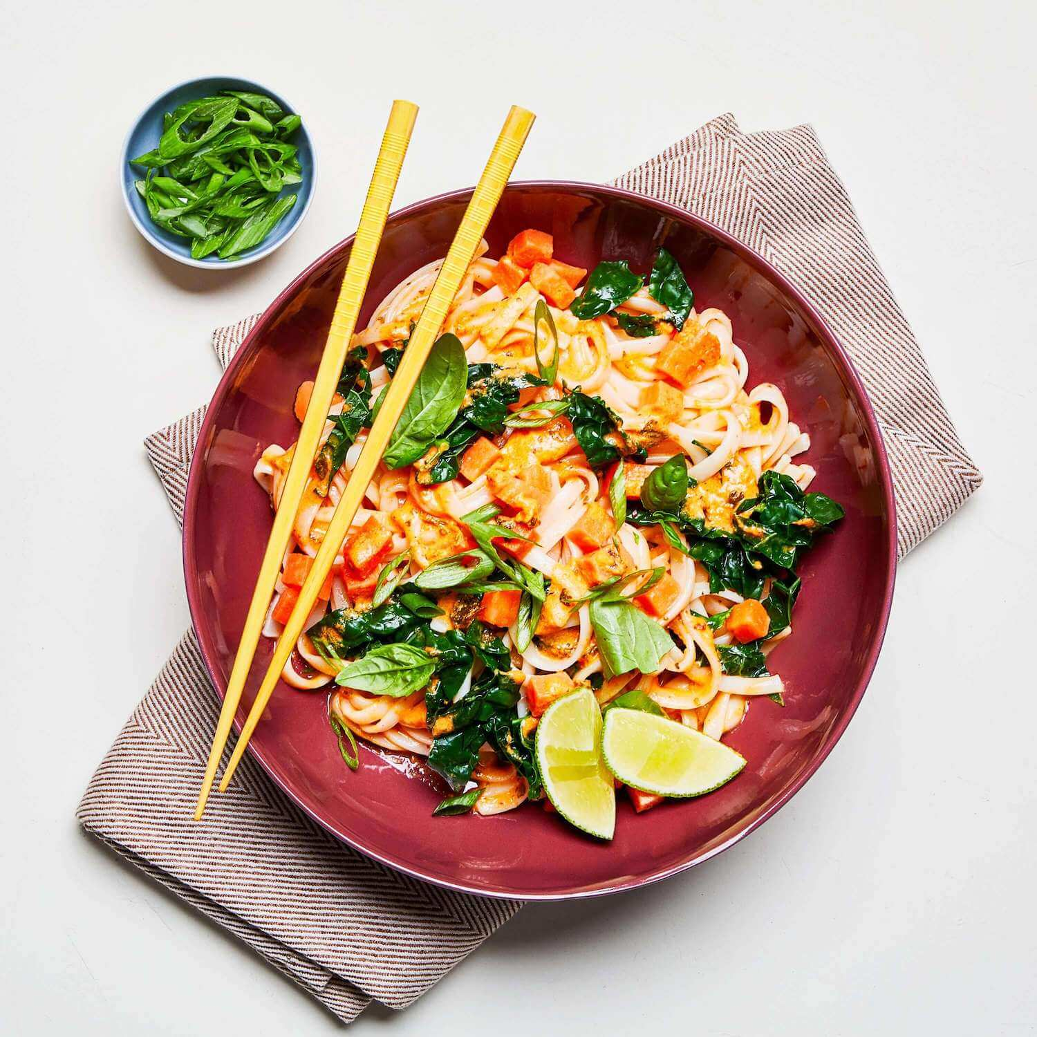 Red Curry Noodles in a dish with chopsticks, a napkin, and scallions on the table.
