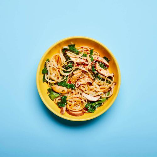 Sesame Noodles in a dish on a blue background.