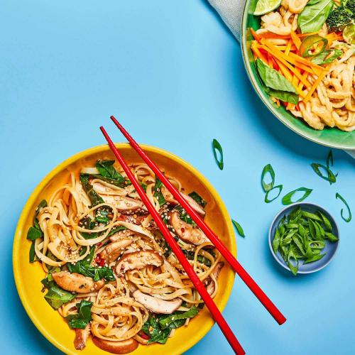 Sesame noodles in a dish with chopsticks on a blue background with scallions and another noodle dish.