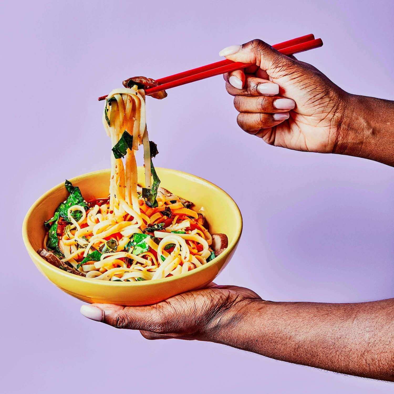 Sesame Noodles in a dish being held by a woman, who is pulling the noodles up out of the bowl with chopsticks.