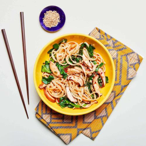Sesame Noodles in a dish with chopsticks and a patterned napkin.