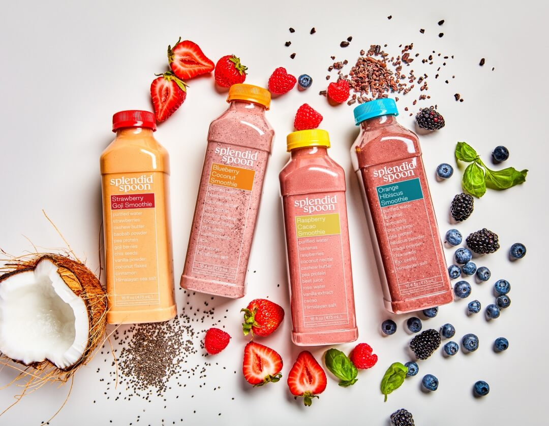 Four smoothies with ingredients around them.