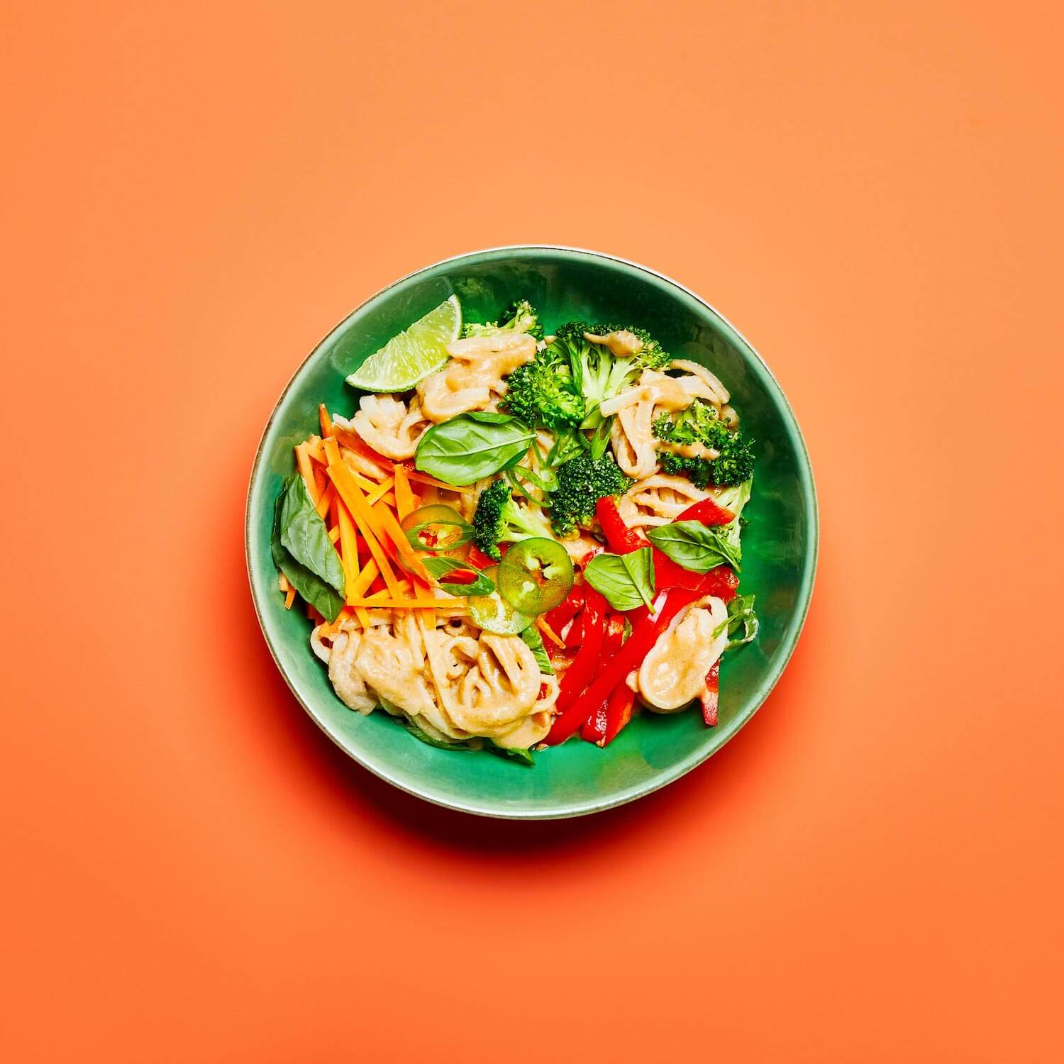 Tangy Ginger Noodles in a dish on an orange background.