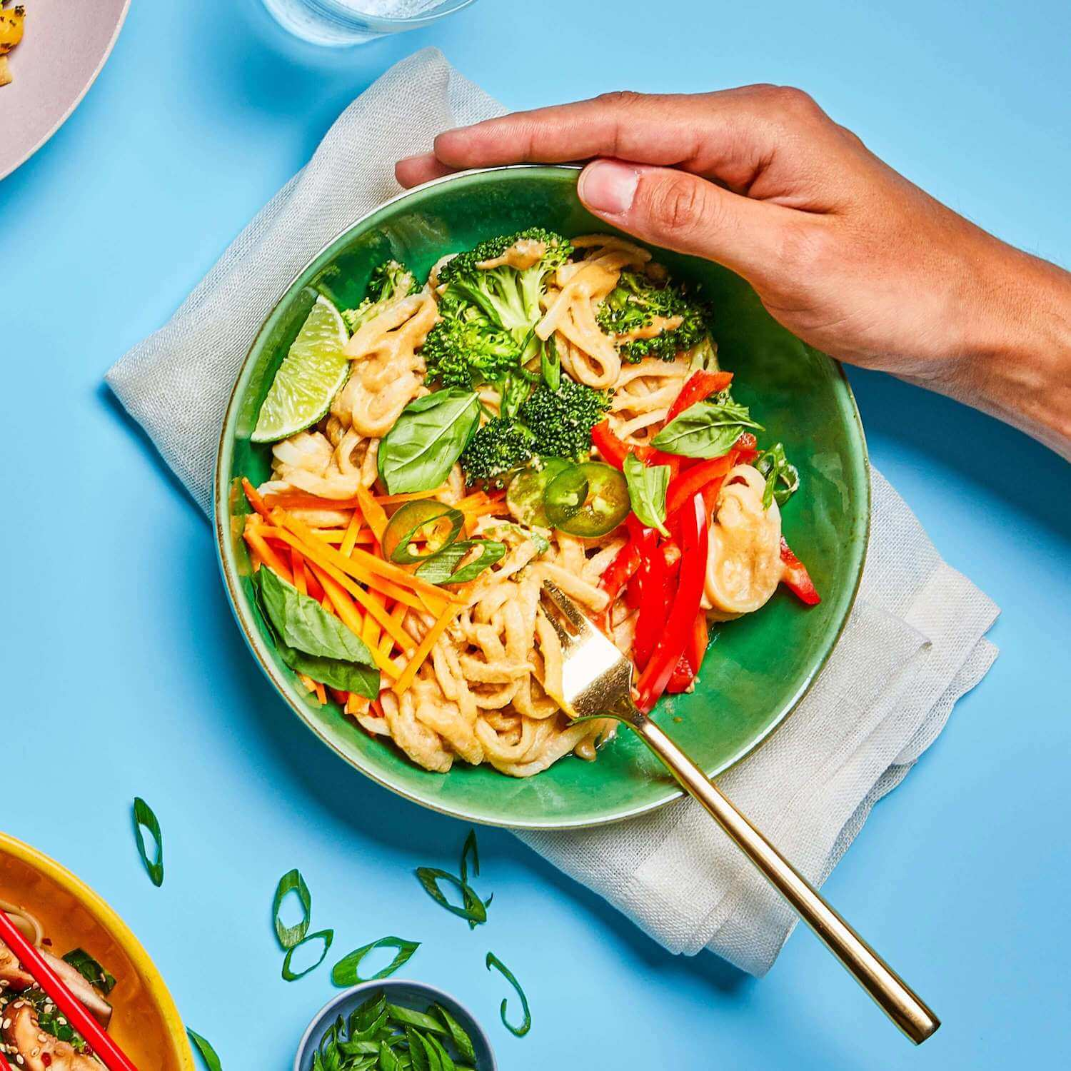 Tangy Ginger Noodles in a dish with a fork in it, on a table with a few other dishes and a napkin.