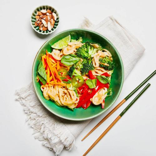 Tangy Ginger Noodles in a dish on a white background with a napkin, chopsticks, and a dish of almonds.